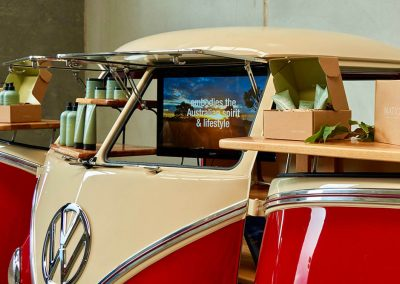 Gallery promo with LCD screen inside a red branded Kombi Van