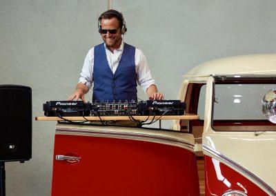 Pop Up Kombi DJ Playing besides red branded Kombi Van Close View