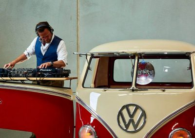 Pop Up Kombi DJ Playing his instrument wearing a headphone beside a red branded kombi van