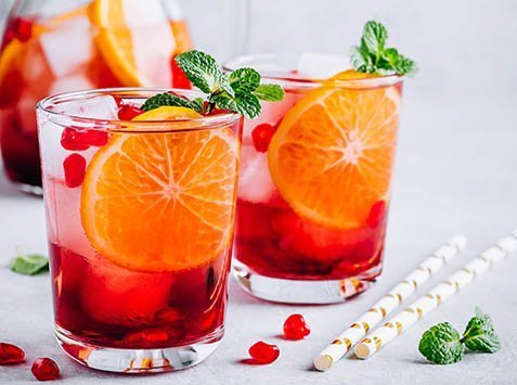 Pomegranate Orange Holiday Punch with ice and mint in glass on gray concrete stone background